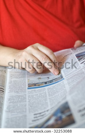 Close up shot of a woman's hand while she's reading the newspaper. Shallow depth of field.