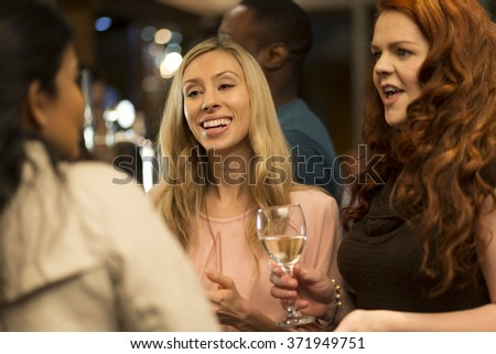 close up shot of a woman talking to her friends at a bar.