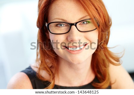 Close-up shot of a wonderful red-haired woman looking at camera - stock photo