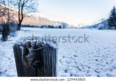close up shot of a wooden post covered with hoarfrost ice crystals in winter - stock photo