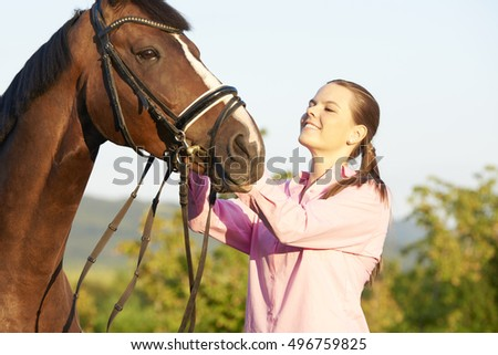Close-up shot of a young woman taking care of her sport horse.