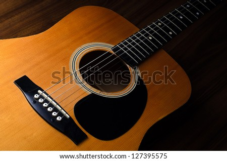Close up shot of acoustic guitar on wooden table - low key - stock photo