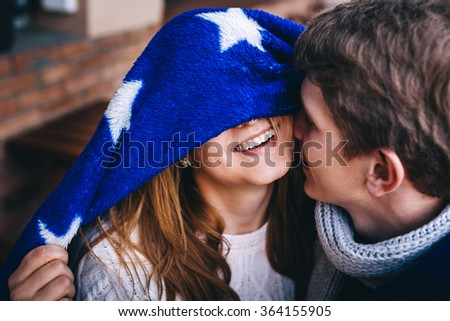 Close up shot of affectionate young couple embracing and kissing outdoors. Beautiful teeth smile of hipster girl hiding her eyes. - stock photo