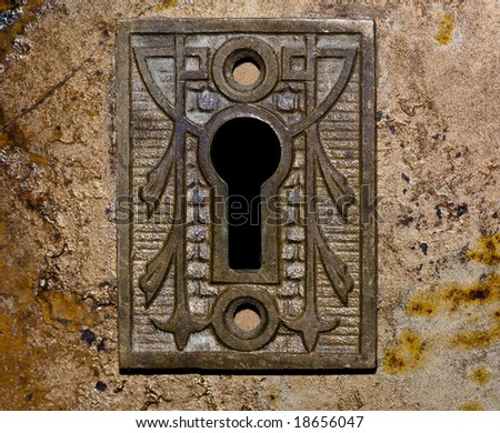 Close-up shot of an antique keyhole in a rusted iron plate on an old wall. - stock photo
