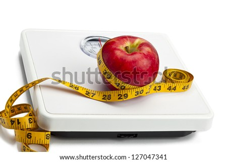Close-up shot of an apple tied in measuring tape on weight machine. - stock photo