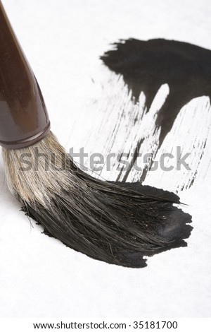 Close-up shot of an Asian traditional writing brush and a calligraphy - stock photo