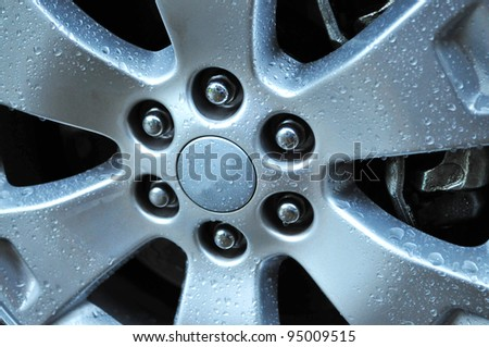Close up shot of an auto wheel with water drops on its surface - stock photo