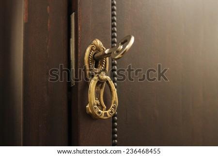 Close-up shot of an old key inside a keyhole - stock photo