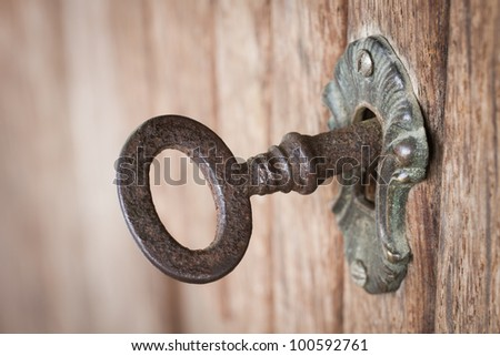 Close-up shot of an old rusty key inside a keyhole - stock photo