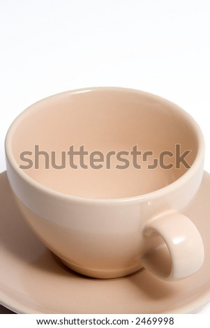 Close up shot of an peach colored coffee cup and saucer. - stock photo