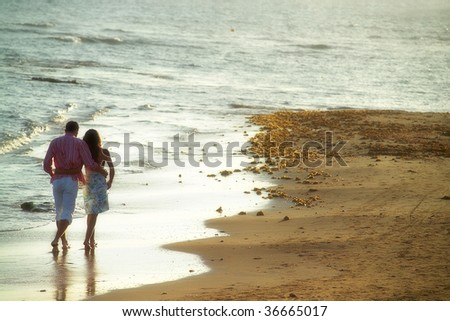 close up shot of attractive couple walking at the beach - stock photo