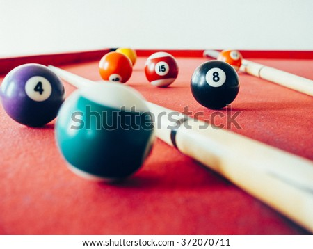 close up shot of 8 Ball from pool or billiards on a billiard table. Selective Focus. film filtered. - stock photo