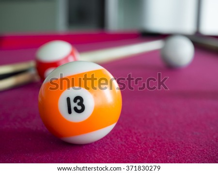 close up shot of 13 Ball from pool or billiards on a billiard table. Selective Focus. The lucky number. - stock photo