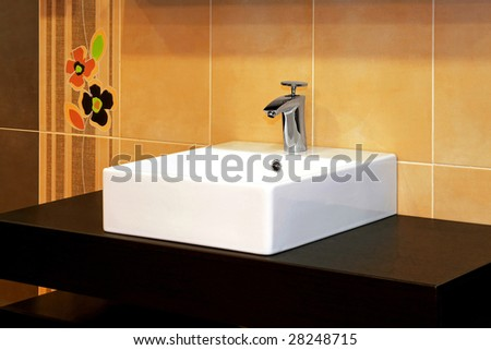 Close up shot of basin and floral tiles - stock photo
