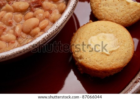 Close up shot of bean soup and buttered corn bread on ceramic dishes