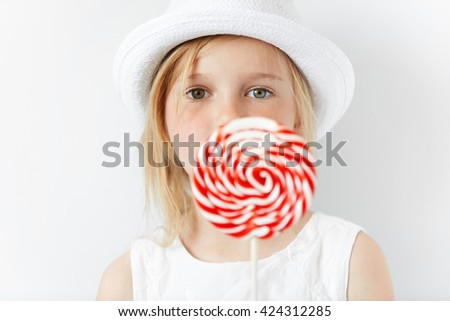 Close up shot of beautiful preschool child in stylish white clothes, enjoying sweet candy, posing against white copy space wall. Beautiful little girl with huge spiral lollipop. Selective focus - stock photo