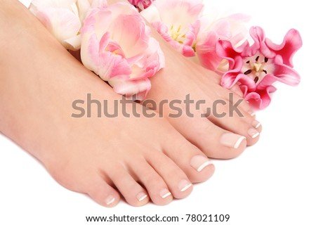 Close-up shot of beautiful woman feet with french pedicure and pink flowers around - stock photo