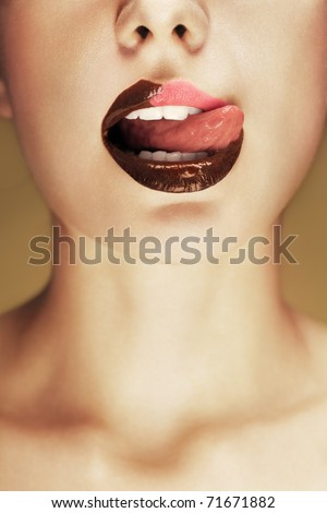 Close-up shot of beautiful woman lips with chocolate, girl licking her lips. Conceptual image. - stock photo