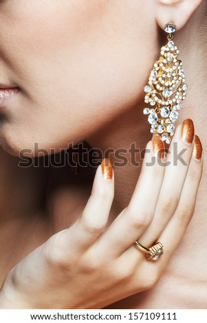Close-up shot of beautiful young woman with vogue shining earring - stock photo