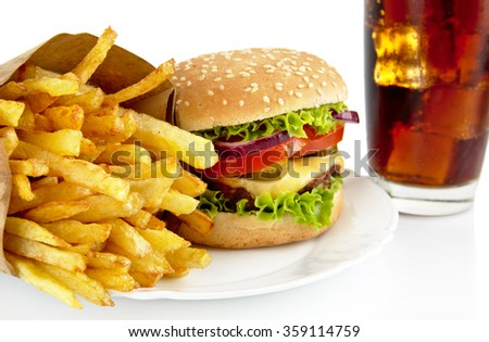 Close up shot of big cheeseburger with french fries and glass of cola on plate