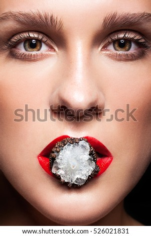 Close up shot of bijouterie ring with stone in red female mouth lips
