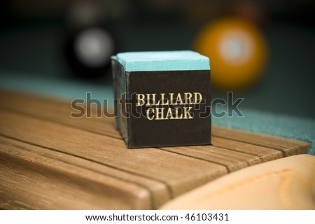 Close up shot of billiard chalk on pool table with balls in background - stock photo