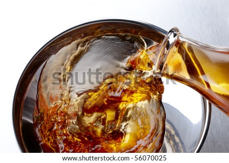 Close up shot of bio fuel being poured into shiny aluminum funnel - stock photo