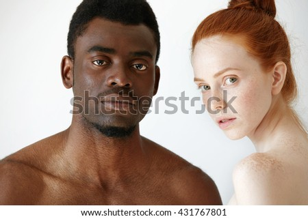 Close up shot of black male and white female posing isolated against white studio wall background. Mixed-race love between young African man and redhead Caucasian woman, looking at the camera - stock photo