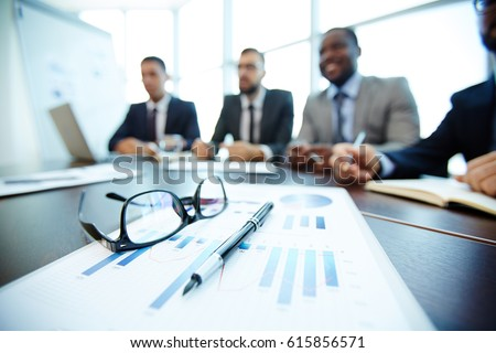 Close-up shot of business documents lying on meeting table, blurred silhouettes of male employees seen on background