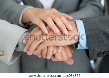 Close-up shot of business people putting their hands together to give support to a new project - stock photo