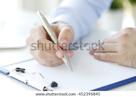 Close-up shot of businessman fill the form. - stock photo