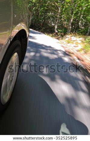 Close up shot of car front wheel while driving in a curve on a mountain road