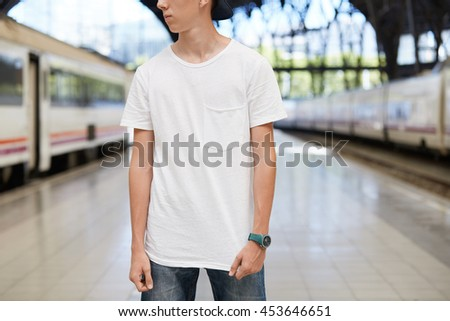 Close up shot of Caucasian schoolboy wearing snapback and blank white copy space T-shirt for your text or advertising content, looking away, standing isolated against urban setting background - stock photo