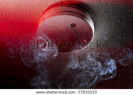 Close up shot of ceiling mounted smoke detector with white smoke and red warning light - stock photo