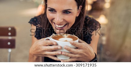 Close up shot of cheerful young woman drinking coffee at a cafe and looking away. Caucasian female enjoying a cup of coffee. - stock photo