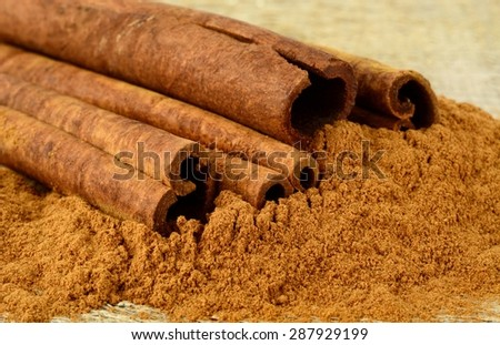 Close-up shot of cinnamon on cinnamon powder on wooden tabl - stock photo