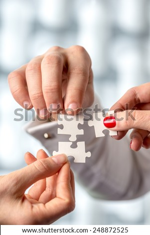 Close up Shot of Conceptual Human Hand Holding White Puzzle Pieces. Emphasizing Problem Solving Concept. - stock photo