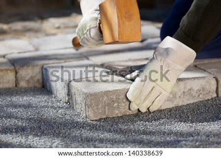 Close up shot of construction worker fixing a brick road - stock photo