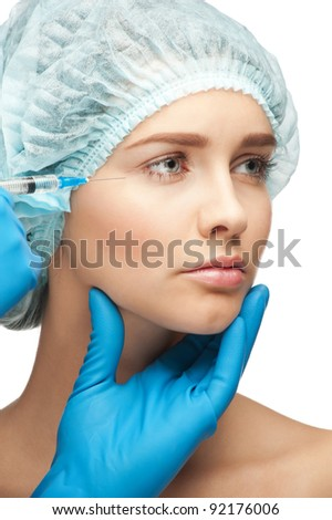 Close-up shot of cosmetic injection to the pretty female face. Isolated on white background - stock photo