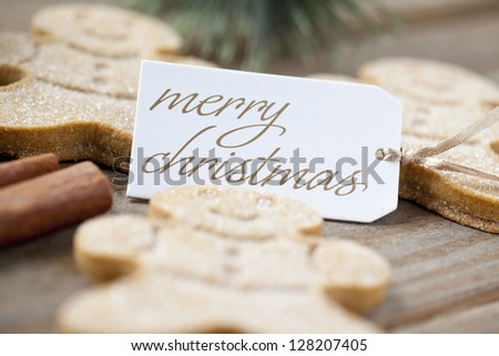 Close-up shot of defocused image of gingerbread with a Merry Christmas tag on top of a wooden plank.