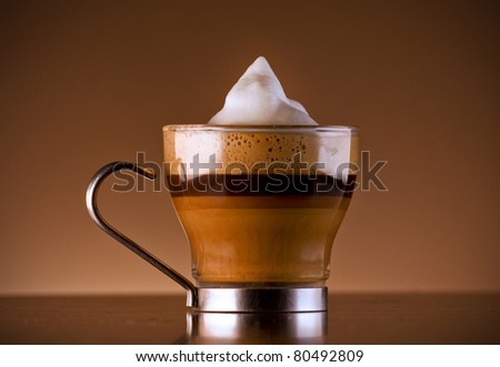 Close-up shot of Delicious coffee drink called caffe macchiato, which is espresso with milk and foam and added chocolate syrup for layered effect. Served on a bar in a glass cup. - stock photo