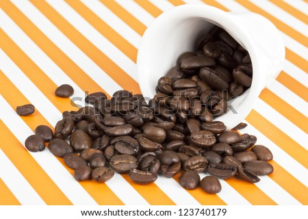 Close-up shot of disposable cup with coffee beans spilled out on stripe surface. - stock photo