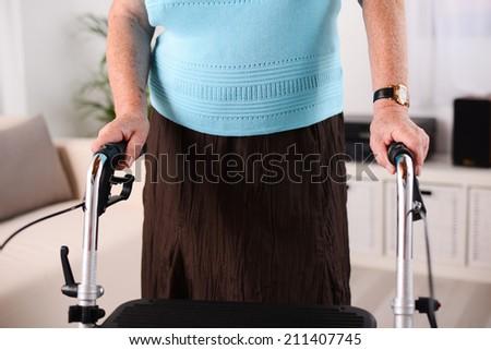 close up shot of elderly woman using walker rehab - stock photo