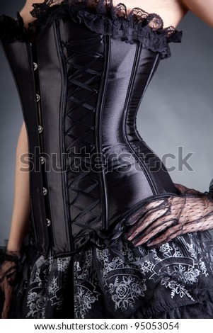 Close-up shot of elegant woman in black corset, studio shot - stock photo
