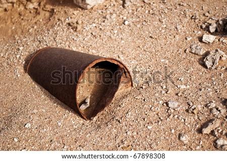close up shot of empty rusty steel jar in the desert - stock photo