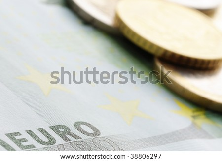 Close up shot of euro note with coins on background. Selective focus on foreground.