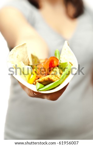 close up shot of fajita being offered by a woman - stock photo
