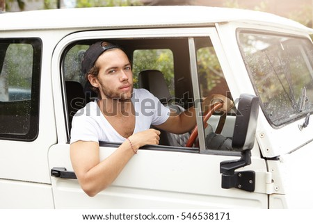Close up shot of fashionable handsome young bearded model posing inside white jeep on driver's seat holding hand on steering wheel and looking at camera with confident expression on his face