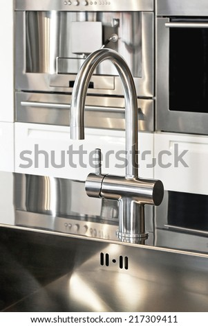 Close up shot of faucet in modern kitchen