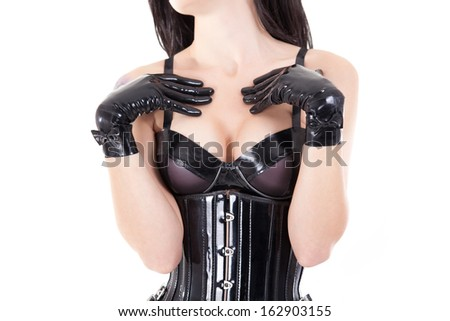 Close-up shot of female breast in latex bra, isolated on white background    - stock photo